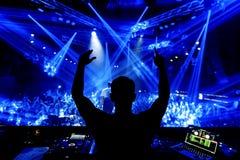 discjockeyhänder upp på nattklubbpartiet under blått ljus med folkmassan av folk royaltyfria foton
