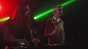discjockeylek för två härlig unga kvinnor musiken på den blandande konsolen i nattklubben stock video