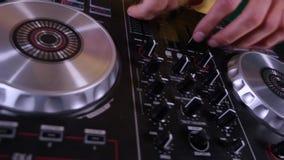 discjockeyn blandar sånger på utrustning, räcker closeupen lager videofilmer