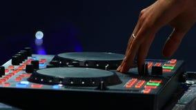 discjockeyn på diskot arbetar bak fjärrkontrollen Dansgolv och ljus musik discjockey i nattklubben lager videofilmer