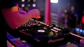 discjockeyn spelar med hans händer på en musikblandare i en nattklubb arkivfilmer