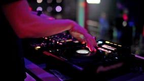 discjockeyn spelar med hans händer på en musikblandare i en nattklubb lager videofilmer