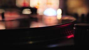 discjockeyn spelar vinylskivtallrikar I en nattklubb - stång arkivfilmer