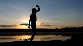 Disco χορών νεαρών άνδρων σε μια τράπεζα λιμνών στο ηλιοβασίλεμα στην slo-Mo φιλμ μικρού μήκους