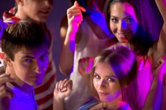 Disco. Smart teenagers looking at camera while dancing at disco royalty free stock images