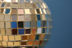 Disco ball. Close-up of a mirrored disco ball on one side with blue background Stock Images