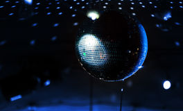 Disco ball with blue rays over dark Stock Photos