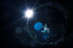 A disco ball with light flare and blurry lights on background. Stock Photos