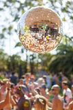 Disco Ball Party. Image of an isolated disco ball against a blurry background.  We can see young people partying and having fun in the background in what appears Stock Photo