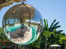Disco ball reflecting green swimming pool. stock image