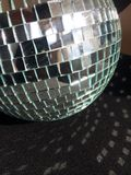 Disco ball with reflection. Mirrored disco ball with light reflecting on to the adjacent black fabric. Small square mirrors on a ball create reflections of light Stock Images