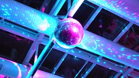 Disco ball rotates under the ceiling in a nightclub stock video