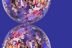 Disco ball with symmetrical reflection on a purple background royalty free stock photography