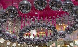 Disco balls hang on pink ropes. Background with a lot of disco balls stock photos