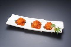 Disco blanco de los huevos rojos del sushi fresco en fondo negro Imagenes de archivo