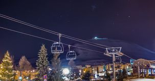 Disco Chair Lift Timelapse 4k. Night timelapse of a mountain, stars, ski lift and people going to a party stock video
