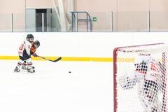 Disco che gioca fra i giocatori dei gruppi di hockey su ghiaccio Immagini Stock Libere da Diritti
