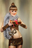 Disco christmas masquerade girl with golden gift Stock Photos