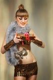Disco christmas masquerade girl with golden gift Stock Photos