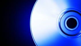 Disco compacto azul de giro en un lazo inconsútil del fondo negro almacen de video