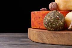 Disco con diversos tipos de queso y de nueces Queso hecho a mano en el tablero de madera Producción de queso Fotografía de archivo libre de regalías