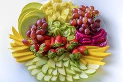 Disco crudo del surtido de las frutas en la placa blanca, en la tabla blanca foto de archivo
