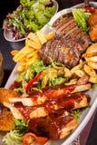 Disco de carnes, de la ensalada y de patatas fritas mezcladas Fotografía de archivo libre de regalías