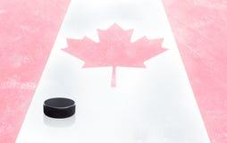Disco de hóquei e bandeira canadense no gelo com espaço da cópia imagens de stock royalty free