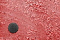 Disco de hóquei no vermelho do gelo Imagem de Stock