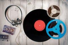 Disco de vinilo, casete, cinta del carrete y auriculares audios negros Imagen de archivo libre de regalías