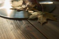 Disco de vinilo del vintage y hojas de otoño imagenes de archivo