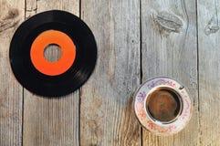 Disco de vinilo y taza de café viejos en una tabla de madera Foto de archivo libre de regalías