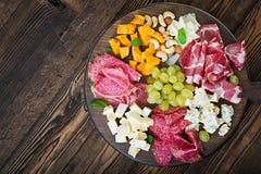 Disco del abastecimiento del Antipasto con tocino, desigual, la salchicha, el queso verde y la uva Imagen de archivo libre de regalías