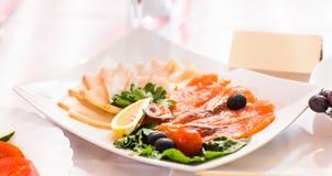 Disco del abastecimiento de la carne y de los pescados curados cortados con la decoración vegetal en la tabla de pascua Fotos de archivo