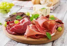 Disco del abastecimiento del Antipasto con tocino, desigual, la salchicha, el queso verde y uvas Foto de archivo libre de regalías