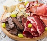 Disco del abastecimiento del Antipasto con tocino, desigual, la salchicha, el queso verde y uvas Imagenes de archivo
