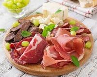Disco del abastecimiento del Antipasto con tocino, desigual, la salchicha, el queso verde y uvas Imágenes de archivo libres de regalías