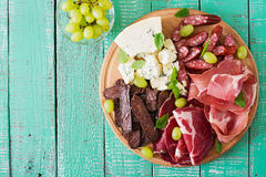 Disco del abastecimiento del Antipasto con tocino, desigual, la salchicha, el queso verde y uvas Fotografía de archivo libre de regalías