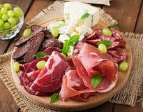 Disco del abastecimiento del Antipasto con tocino, desigual, la salchicha, el queso verde y uvas Foto de archivo