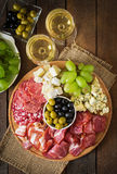 Disco del abastecimiento del Antipasto con tocino, desigual, salami, queso y uvas Fotos de archivo libres de regalías
