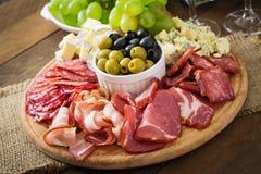 Disco del abastecimiento del Antipasto con tocino, desigual, salami, queso y uvas Imágenes de archivo libres de regalías
