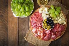 Disco del abastecimiento del Antipasto con tocino, desigual, salami, queso y uvas Foto de archivo libre de regalías