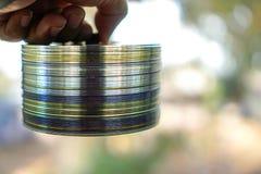 Disco del CD impilato su una cazzuola della mano sugli uomini fotografia stock libera da diritti