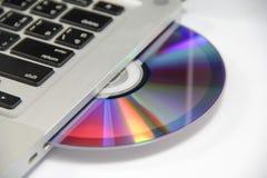 Disco del Cd o del dvd en computadora portátil Fotos de archivo