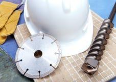 Disco del diamante, taladro y un casco en una teja. Aún-vida Imagen de archivo