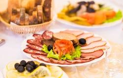 Disco del jamón cortado, del salami y de la carne curada con la decoración vegetal en la tabla festiva Imagen de archivo