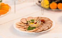 Disco del jamón cortado, del salami y de la carne curada con la decoración vegetal en la tabla festiva Imágenes de archivo libres de regalías