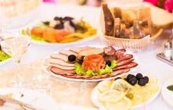 Disco del jamón cortado, del salami y de la carne curada con la decoración vegetal en la tabla festiva Fotografía de archivo libre de regalías