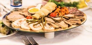 Disco del jamón cortado, del salami y de la carne curada con la decoración vegetal en la tabla festiva Imagenes de archivo