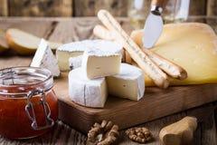 Disco del queso con el vino, el atasco y las nueces en el tablero de madera imagen de archivo